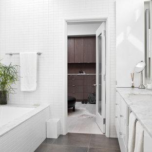 Стильный дизайн: главная ванная комната среднего размера в современном стиле с плоскими фасадами, белыми фасадами, полновстраиваемой ванной, унитазом-моноблоком, белой плиткой, керамической плиткой, белыми стенами, полом из керамогранита, врезной раковиной и мраморной столешницей - последний тренд