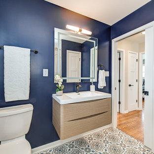 Diseño de cuarto de baño con ducha, contemporáneo, de tamaño medio, con armarios con paneles lisos, puertas de armario de madera clara, sanitario de dos piezas, paredes azules, suelo de baldosas de cerámica, lavabo integrado, encimera de cuarzo compacto, suelo multicolor y encimeras blancas