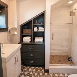 Modelo de cuarto de baño minimalista, pequeño, con lavabo tipo consola, armarios tipo mueble, puertas de armario grises, ducha empotrada, sanitario de dos piezas, baldosas y/o azulejos marrones, baldosas y/o azulejos de cemento, paredes blancas y suelo con mosaicos de baldosas
