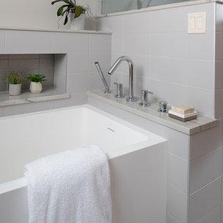Стильный дизайн: главная ванная комната среднего размера в современном стиле с ванной в нише, душем в нише, серой плиткой, керамической плиткой, серыми стенами, полом из керамогранита, столешницей из кварцита, серым полом, душем с распашными дверями, серой столешницей, нишей, встроенной тумбой и панелями на стенах - последний тренд