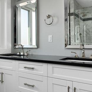 Modelo de cuarto de baño principal, clásico renovado, de tamaño medio, con armarios estilo shaker, puertas de armario blancas, ducha a ras de suelo, paredes grises, suelo vinílico, lavabo bajoencimera, encimera de cuarzo compacto, suelo multicolor, ducha con puerta con bisagras y encimeras negras