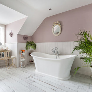 Design ideas for a mid-sized traditional bathroom in Sussex with a freestanding tub, pink walls and white floor.