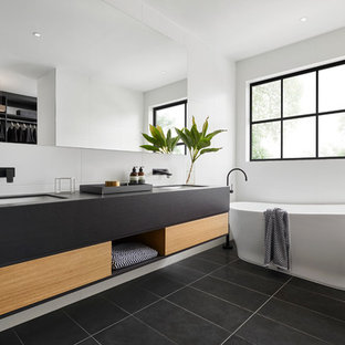 Contemporary 3/4 bathroom in Melbourne with flat-panel cabinets, black cabinets, a freestanding tub, white tile, white walls, an undermount sink and black floor.