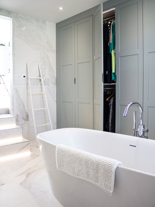 Mid-sized trendy master freestanding bathtub photo in London with gray  cabinets