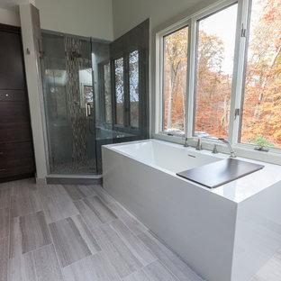 Foto på ett stort funkis en-suite badrum, med ett undermonterad handfat, släta luckor, skåp i mörkt trä, bänkskiva i återvunnet glas, ett fristående badkar, en hörndusch, en toalettstol med separat cisternkåpa, grå kakel, porslinskakel, grå väggar och travertin golv