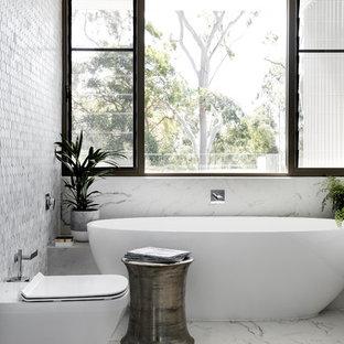 Новые идеи обустройства дома: ванная комната среднего размера в современном стиле с плоскими фасадами, белыми фасадами, отдельно стоящей ванной, унитазом-моноблоком, разноцветной плиткой, металлической плиткой, разноцветными стенами, настольной раковиной, столешницей из дерева, разноцветным полом и мраморным полом