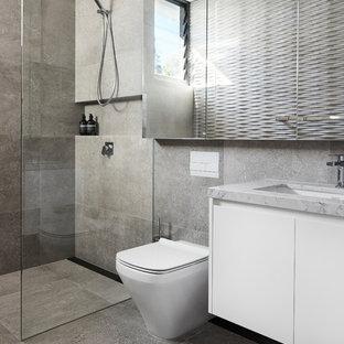 Foto di una stanza da bagno contemporanea di medie dimensioni con ante lisce, ante bianche, doccia aperta, WC monopezzo, piastrelle grigie, lastra di pietra, pareti grigie, pavimento in ardesia, lavabo da incasso, top in marmo, pavimento grigio e doccia aperta