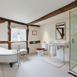 Inspiration for a rural ensuite bathroom in London with a claw-foot bath, a corner shower, a two-piece toilet, beige walls, a wall-mounted sink, beige floors and a hinged door.