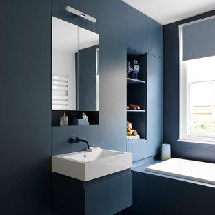 Ispirazione per una stanza da bagno per bambini minimal con ante lisce, ante blu, vasca da incasso, pareti blu, lavabo sospeso e pavimento blu