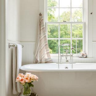 На фото: ванная комната в стиле кантри с отдельно стоящей ванной, белыми стенами и панелями на стенах