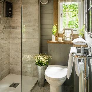 Ejemplo de cuarto de baño principal, rústico, pequeño, con ducha esquinera, sanitario de una pieza, baldosas y/o azulejos grises, baldosas y/o azulejos de cerámica, paredes grises, suelo de madera clara, encimera de madera, suelo gris y ducha abierta