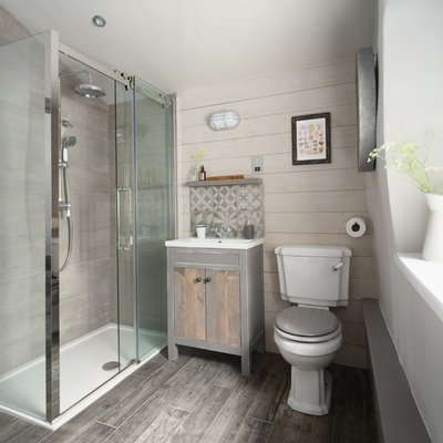 Small beach style gray tile gray floor bathroom photo in Other with flat-panel cabinets, light wood cabinets, a two-piece toilet, a console sink and beige walls