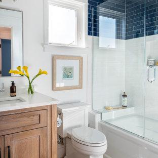 Exemple d'une salle de bain bord de mer avec un placard à porte shaker, des portes de placard en bois brun, une baignoire en alcôve, un combiné douche/baignoire, un carrelage bleu, un carrelage blanc, un mur blanc, un lavabo encastré, un sol beige, une cabine de douche à porte battante, un plan de toilette blanc, meuble-lavabo sur pied et meuble simple vasque.