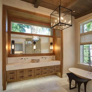 На фото: с высоким бюджетом огромные главные ванные комнаты в современном стиле с плоскими фасадами, фасадами цвета дерева среднего тона, отдельно стоящей ванной, мраморным полом, врезной раковиной, мраморной столешницей, каменной плиткой, бежевыми стенами, серой плиткой, белой плиткой, белым полом и белой столешницей