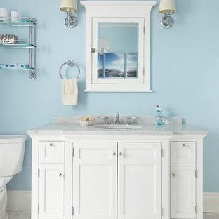Modelo de cuarto de baño con ducha, clásico, grande, con armarios con paneles empotrados, puertas de armario blancas, bañera con patas, ducha esquinera, sanitario de una pieza, baldosas y/o azulejos blancos, baldosas y/o azulejos de cerámica, paredes azules, suelo de mármol, lavabo bajoencimera y encimera de acrílico