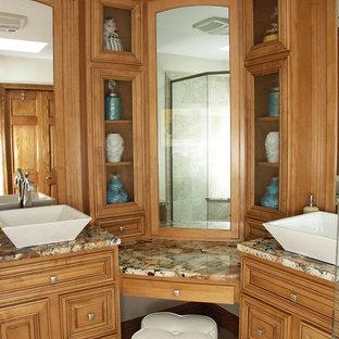 ニューヨークの中くらいのトラディショナルスタイルのおしゃれなバスルーム (浴槽なし) (レイズドパネル扉のキャビネット、中間色木目調キャビネット、コーナー設置型シャワー、分離型トイレ、ベージュのタイル、セラミックタイル、ベージュの壁、セラミックタイルの床、ベッセル式洗面器、オニキスの洗面台、ベージュの床、開き戸のシャワー) の写真