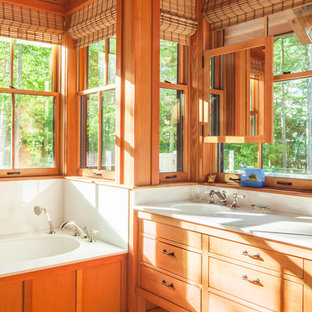 Photo of an arts and crafts master bathroom in Portland Maine with medium wood cabinets, an undermount tub, an undermount sink and flat-panel cabinets.