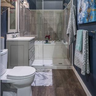 Idee per una piccola stanza da bagno padronale moderna con ante in stile shaker, ante grigie, vasca ad alcova, zona vasca/doccia separata, WC a due pezzi, piastrelle grigie, pareti blu, parquet scuro, lavabo sottopiano, top in quarzo composito e porta doccia scorrevole