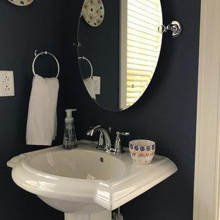 クリーブランドの小さいトランジショナルスタイルのおしゃれなバスルーム (浴槽なし) (フラットパネル扉のキャビネット、白いキャビネット、アルコーブ型シャワー、分離型トイレ、青い壁、クッションフロア、ペデスタルシンク、茶色い床、引戸のシャワー) の写真