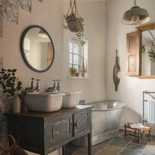 Modelo de cuarto de baño campestre con armarios con paneles con relieve, puertas de armario con efecto envejecido, bañera exenta, paredes beige, lavabo sobreencimera, encimera de madera, suelo negro y encimeras negras