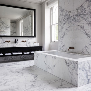 Photo of a contemporary ensuite bathroom in London with open cabinets, black cabinets, a submerged bath, white tiles, marble tiles, marble flooring and white floors.