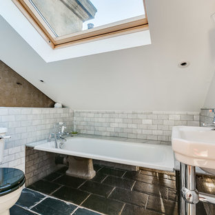 This is an example of a small contemporary shower room in London with white tiles, marble tiles, white walls, a console sink, black floors, a two-piece toilet and an alcove bath.