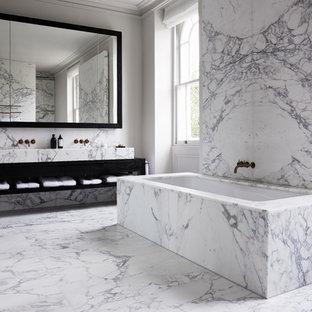 Immagine di una grande stanza da bagno padronale contemporanea con piastrelle di marmo, pavimento in marmo, top in marmo, pareti grigie, nessun'anta, ante nere e vasca sottopiano