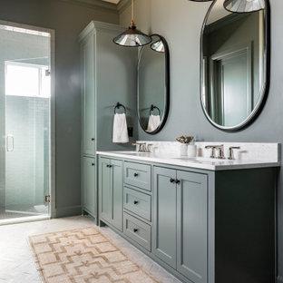 Klassisk inredning av ett stort vit vitt en-suite badrum, med grå skåp, grå kakel, keramikplattor, grå väggar, tegelgolv, dusch med gångjärnsdörr, luckor med infälld panel, ett undermonterad handfat och grått golv