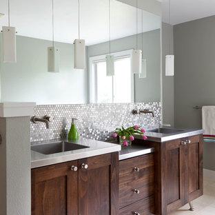 デンバーのコンテンポラリースタイルのおしゃれなマスターバスルーム (一体型シンク、シェーカースタイル扉のキャビネット、濃色木目調キャビネット、ステンレスの洗面台、メタルタイル、グレーの壁、磁器タイルの床) の写真