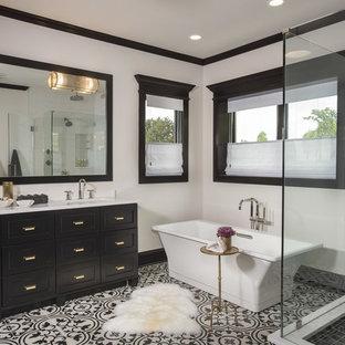 Klassisk inredning av ett stort en-suite badrum, med skåp i shakerstil, svarta skåp, ett fristående badkar, en dusch i en alkov, en toalettstol med separat cisternkåpa, vit kakel, porslinskakel, vita väggar, klinkergolv i porslin, ett undermonterad handfat, bänkskiva i akrylsten, flerfärgat golv och dusch med gångjärnsdörr