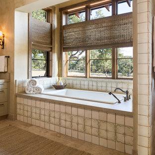Imagen de cuarto de baño rural con armarios estilo shaker, puertas de armario beige, bañera encastrada y baldosas y/o azulejos beige