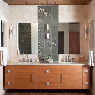 Foto de cuarto de baño principal, contemporáneo, grande, con lavabo bajoencimera, armarios con paneles lisos, puertas de armario de madera oscura, encimera de mármol, sanitario de pared, baldosas y/o azulejos verdes, baldosas y/o azulejos de cerámica, paredes beige, suelo de mármol, bañera exenta y encimeras beige