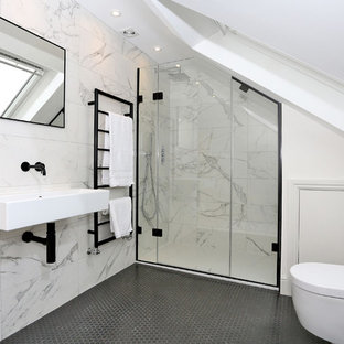 This is an example of a medium sized contemporary wet room bathroom in London with a one-piece toilet, grey tiles, white tiles, marble tiles, white walls, a wall-mounted sink, grey floors and a hinged door.