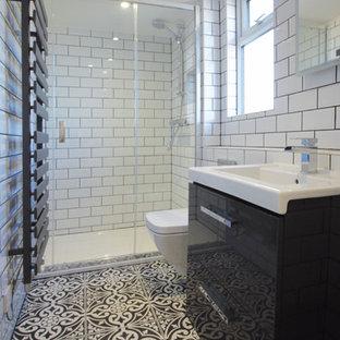 Immagine di una piccola stanza da bagno padronale moderna con ante lisce, ante nere, doccia ad angolo, WC sospeso, piastrelle in ceramica, pareti bianche, pavimento con piastrelle in ceramica, lavabo sospeso, pavimento multicolore e porta doccia scorrevole