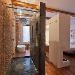 Inredning av ett modernt badrum, med ett fristående badkar och skifferkakel