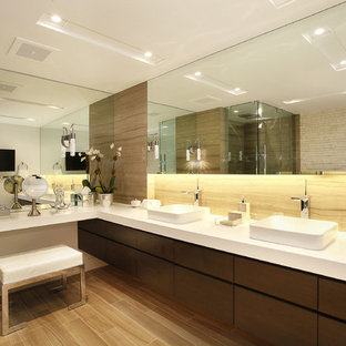 Example of a trendy stone slab freestanding bathtub design in Miami with a vessel sink, flat-panel cabinets, dark wood cabinets and quartz countertops