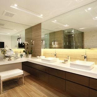 Foto på ett funkis badrum, med ett fristående handfat, släta luckor, skåp i mörkt trä, bänkskiva i kvarts, ett fristående badkar och stenhäll
