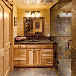 Idées déco pour une douche en alcôve montagne avec un lavabo encastré, un placard à porte plane, un carrelage de pierre et des portes de placard en bois brun.