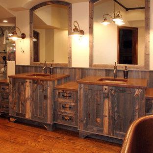Aménagement d'une grand salle de bain principale montagne avec un lavabo encastré, des portes de placard en bois brun, une baignoire indépendante, un mur beige, un sol en bois brun, un placard à porte shaker et un plan de toilette en cuivre.