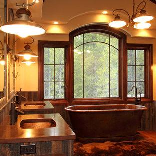 Esempio di una grande stanza da bagno padronale stile rurale con lavabo sottopiano, ante in legno scuro, vasca freestanding, pareti beige, pavimento in legno massello medio, ante in stile shaker e top in rame