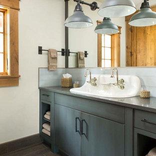 Foto de cuarto de baño rural con lavabo de seno grande, armarios con paneles lisos, puertas de armario grises y paredes blancas