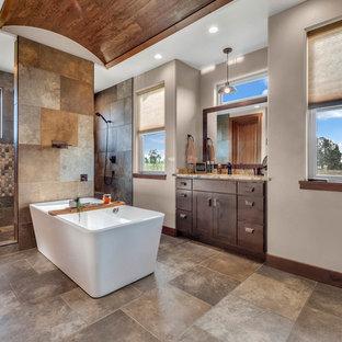 Diseño de cuarto de baño rústico, de tamaño medio, con puertas de armario de madera en tonos medios, bañera exenta, ducha doble, baldosas y/o azulejos de travertino, suelo de travertino, lavabo bajoencimera, encimera de granito, armarios estilo shaker, baldosas y/o azulejos marrones, paredes grises, suelo marrón y encimeras marrones