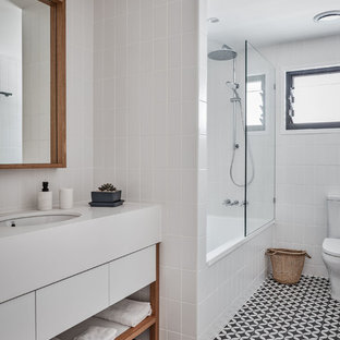 Beach style 3/4 bathroom in Gold Coast - Tweed with flat-panel cabinets, white cabinets, an alcove tub, a shower/bathtub combo, white tile, subway tile, white walls, cement tiles, black floor, white benchtops and an undermount sink.