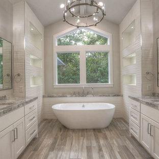 Großes Klassisches Badezimmer En Suite mit Schrankfronten im Shaker-Stil, weißen Schränken, freistehender Badewanne, weißen Fliesen, Porzellanfliesen, Granit-Waschbecken/Waschtisch, Eckdusche, grauer Wandfarbe, Unterbauwaschbecken, Falttür-Duschabtrennung, braunem Holzboden und grauem Boden in Houston