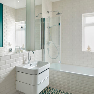 Photo of a contemporary bathroom in London with flat-panel cabinets, white cabinets, a built-in bath, a shower/bath combination, a wall mounted toilet, white tiles, metro tiles, white walls, a wall-mounted sink and multi-coloured floors.