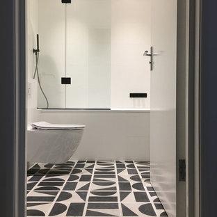 Immagine di una piccola stanza da bagno minimalista con ante lisce, vasca da incasso, vasca/doccia, WC sospeso, pistrelle in bianco e nero, piastrelle in ceramica, pareti bianche, pavimento con piastrelle in ceramica, lavabo sospeso e top in superficie solida