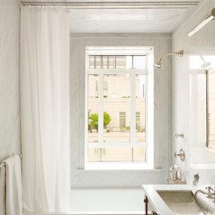 Esempio di una piccola stanza da bagno padronale tradizionale con lavabo sottopiano, ante in legno scuro, vasca ad alcova, vasca/doccia, piastrelle bianche, lastra di pietra, pareti bianche, top in marmo e ante lisce