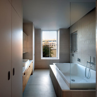 This is an example of a contemporary ensuite bathroom in London with flat-panel cabinets, medium wood cabinets, a built-in bath, a shower/bath combination, grey tiles, grey walls, a vessel sink, grey floors, an open shower and white worktops.