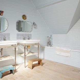 Shabby-Chic-Style Badezimmer mit Waschtischkonsole, Einbaubadewanne, weißen Fliesen, Metrofliesen, weißer Wandfarbe und hellem Holzboden in London