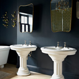 Elegant light wood floor bathroom photo in London with a pedestal sink and black walls